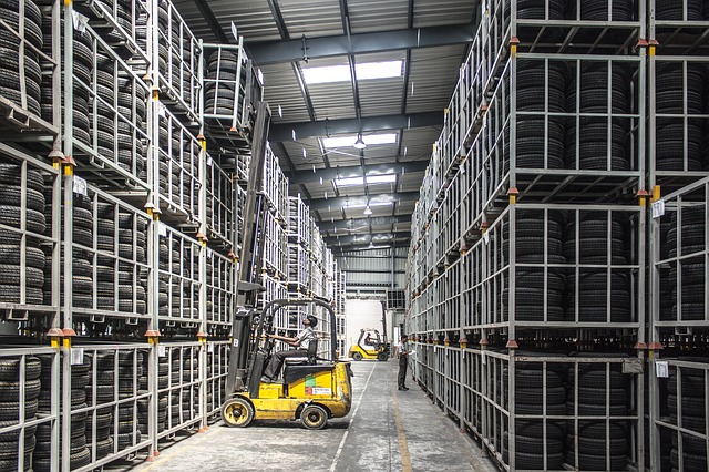 A forklift in a giant warehouse of tires in metal racks. Pictures like this make me shudder when I think of how companies have high inventory levels.